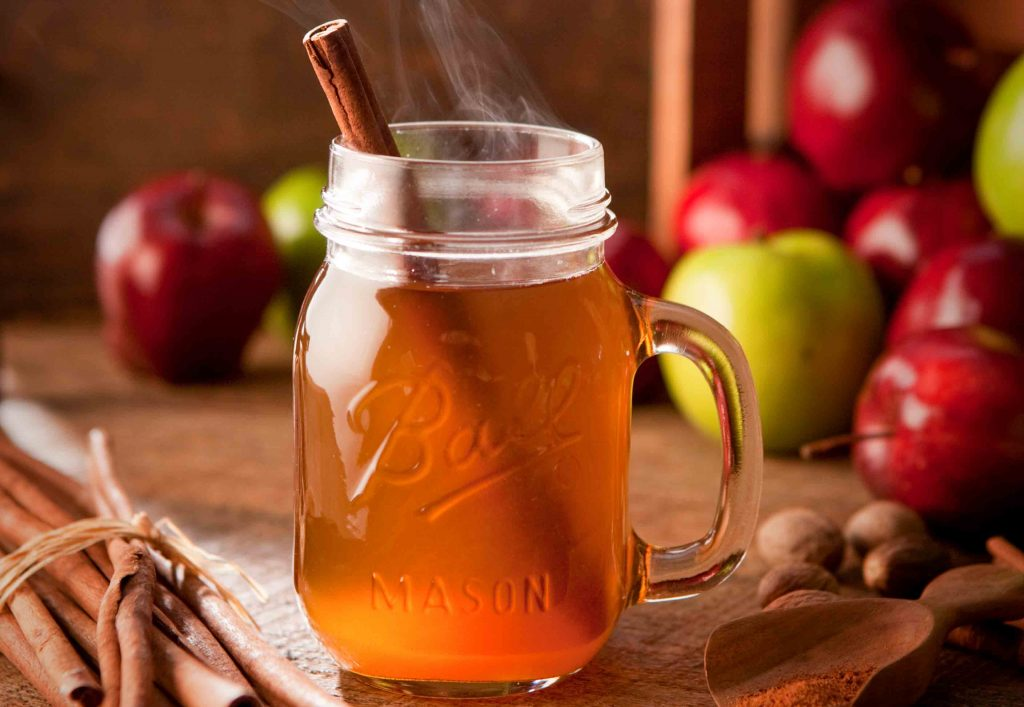 Warm apple cider in a mason jar with a cinnamon stick. Cozy fall scene with warm drink.