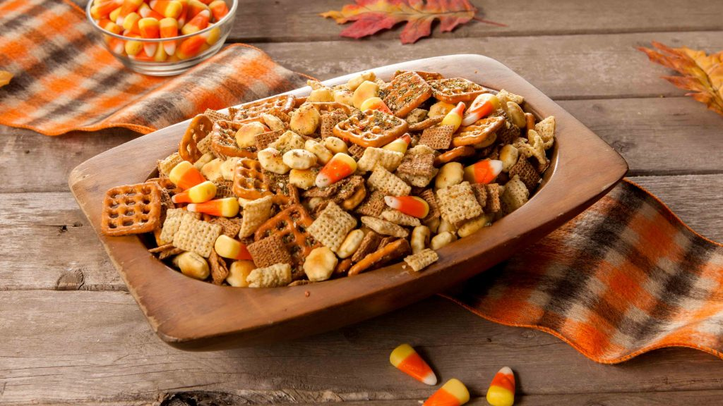 Fall party cereal mix snack with corn candies, checked cereal, and pretzels.